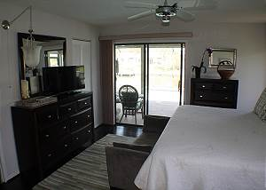 Master bedroom with king size bed and flat screen TV.
