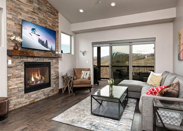 Main level living room with TV, gas fireplace, balcony with BBQ and comfortable seating