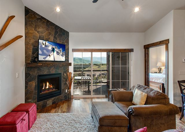 "Living Room with 50"" HD TV, ceiling fan, gas fireplace PLUS walk-out balcony with seating, BBQ and amazing views!"