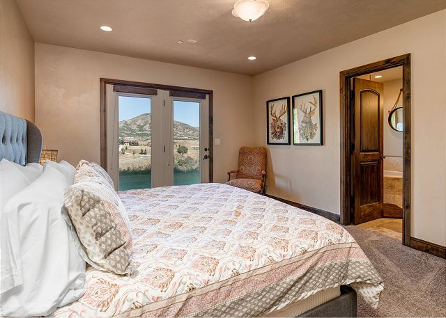 Lower level King master bedroom with TV and walk out door to hot tub patio