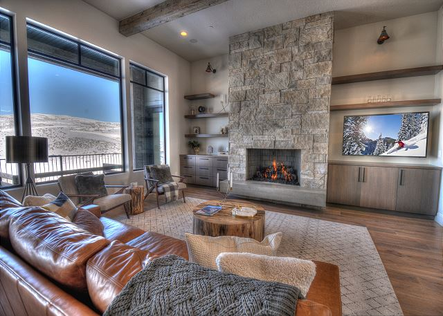 "Main Level Living Area with 65"" HD Smart TV and Open Fireplace. Enjoy this bright, open gathering area!"