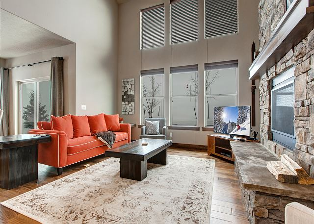 """The beautifully-decorated, open main level features a gorgeous living room with plenty of seating, a 60"""" HD TV with Apple TV hooked up, a cozy gas fireplace."""