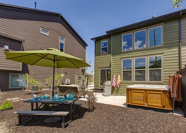 Rear exterior with comfortable seating, dining table, hot tub, patio heater and BBQ