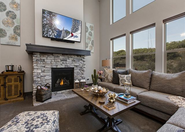 Living room with gas fireplace, TV and large windows to let the gorgeous mountains in!