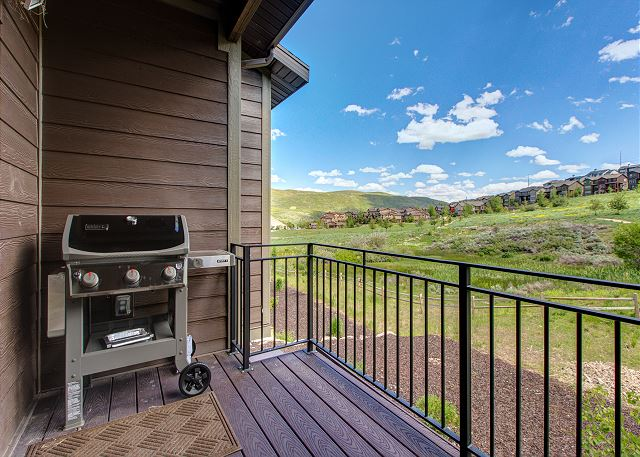 Balcony off of kitchen with seating and gas BBQ