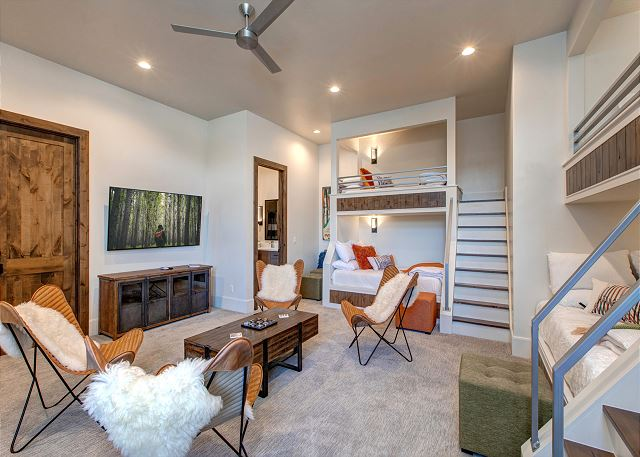 "The fifth bedroom is located on the entry level and is a wonderful flex space. It is a sizable room with three, twin over full-size, custom built-in bunk beds. It offers an entertaining/gaming space with table and chairs, a 65"" Smart TV with Sonos, and Xb"