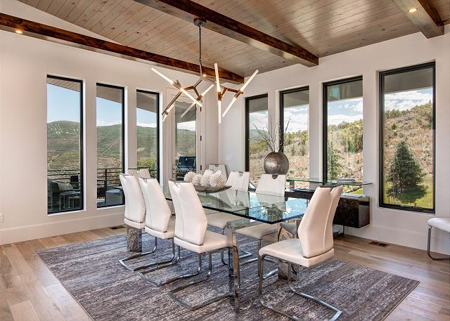 Dining Room: The dining area is stunning with its glass top table with seating for up to 12 and exquisite views throughout. Step out onto a massive deck to enjoy the mountain fresh air and views.  Adorned with a new gas BBQ grill, dining table for 10 and