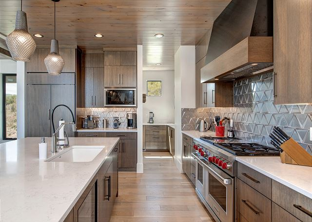 Kitchen: Gourmet kitchen is quite impressive with its stunning cabinetry and finishes, quartz counters, new high-end stainless-steel appliances, and a butler's pantry. It is fully equipped and features a Wolf six-burner plus griddle gas range with double