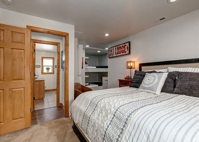 LARGE bedroom with King bed and Queen-over-Queen built-in bunk beds. Each area of the bedroom has its own 4k Ultra HD Samsung Smart TV and there is a curtain to separate the sleeping areas.